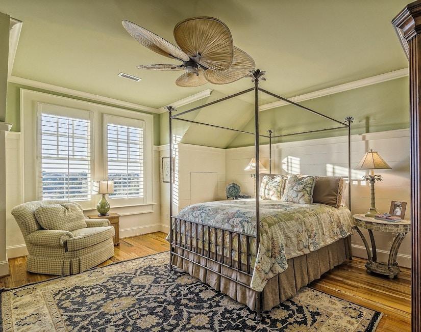 Helles Schlafzimmer mit Teppich, blassgrüner Decke, Deckenventilator und Boxspringbett