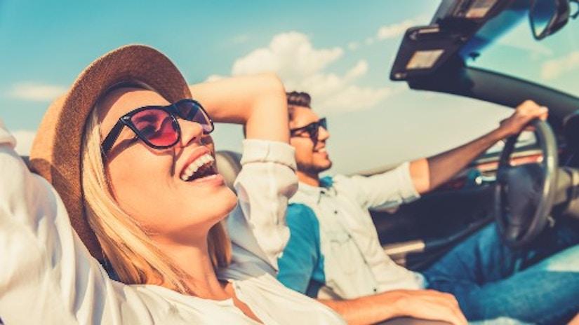 Ein Pärchen sitzt im offenen Cabrio und lacht