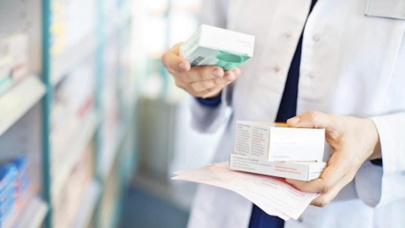 Ein Apotheker, der Pillenpackungen in der Hand hat