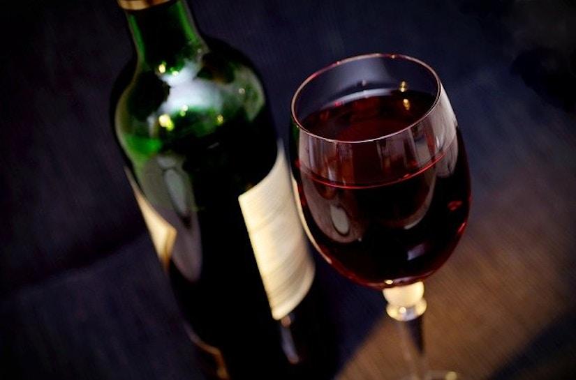 Glas Rotwein und Rotweinflasche