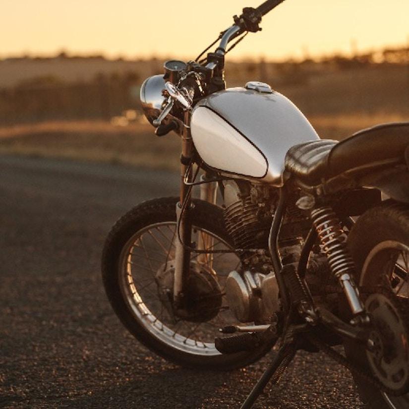 Ein Motorrad, das auf einer einsamen Straße steht