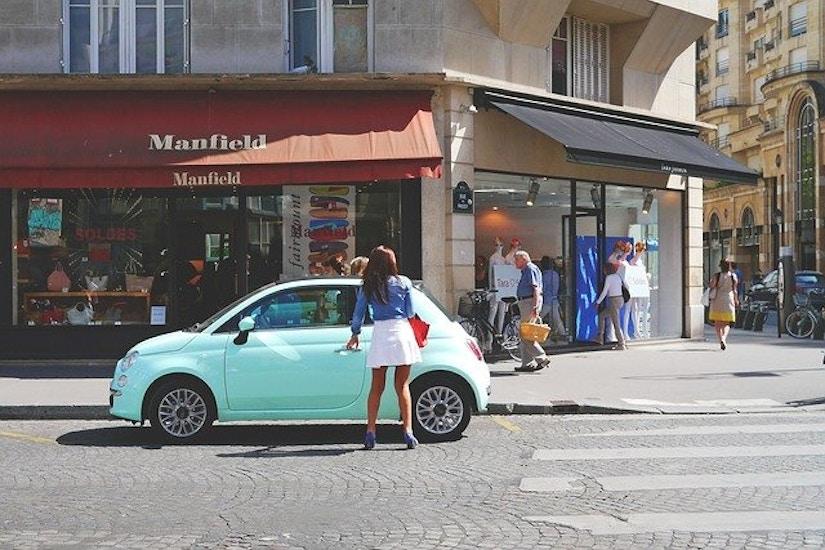 Frau steigt in italienischer Einkaufsmeile in einen mintgrünen Fiat ein