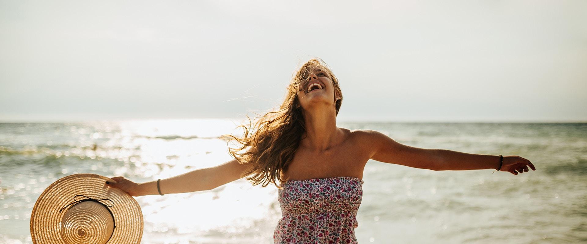 Eine Frau steht am Strand und lacht.
