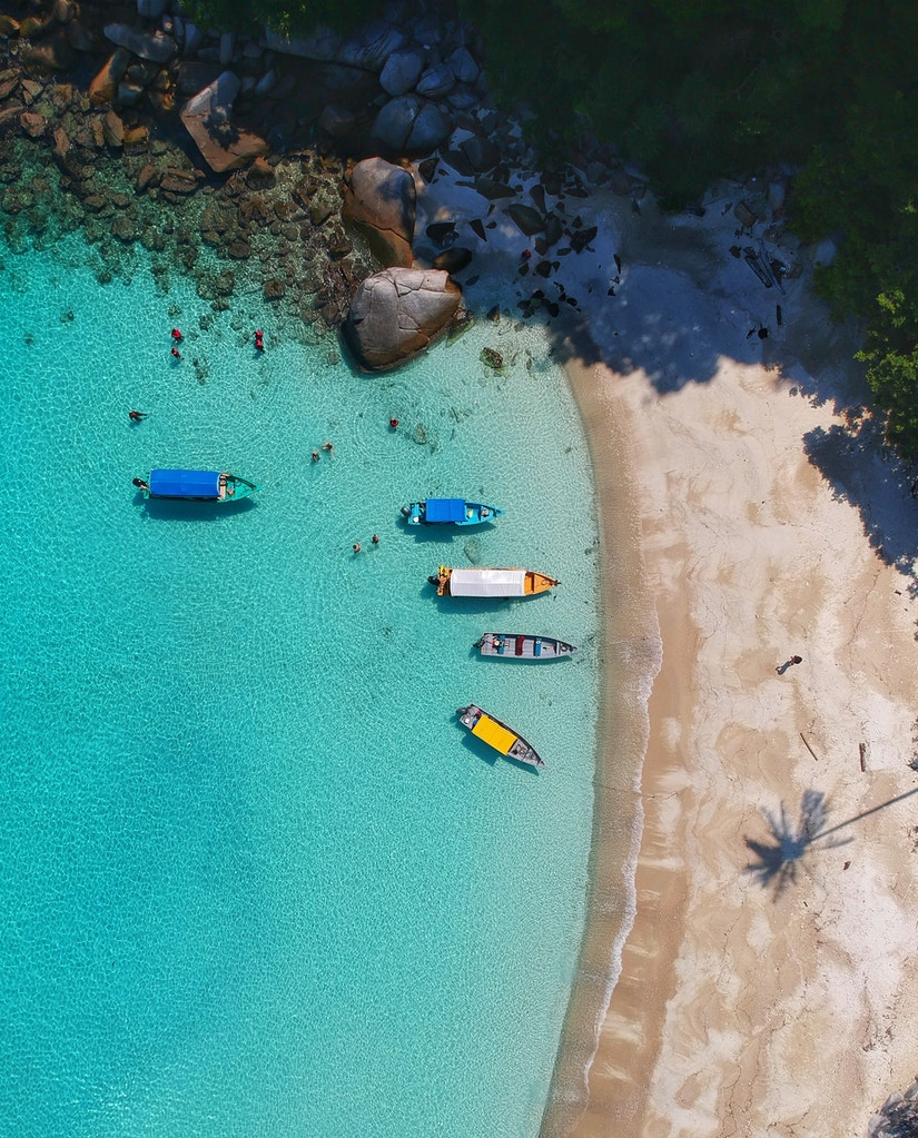 Vogelperspektive auf sonnigen Strand mit azurblauem Wasser und bunten Booten