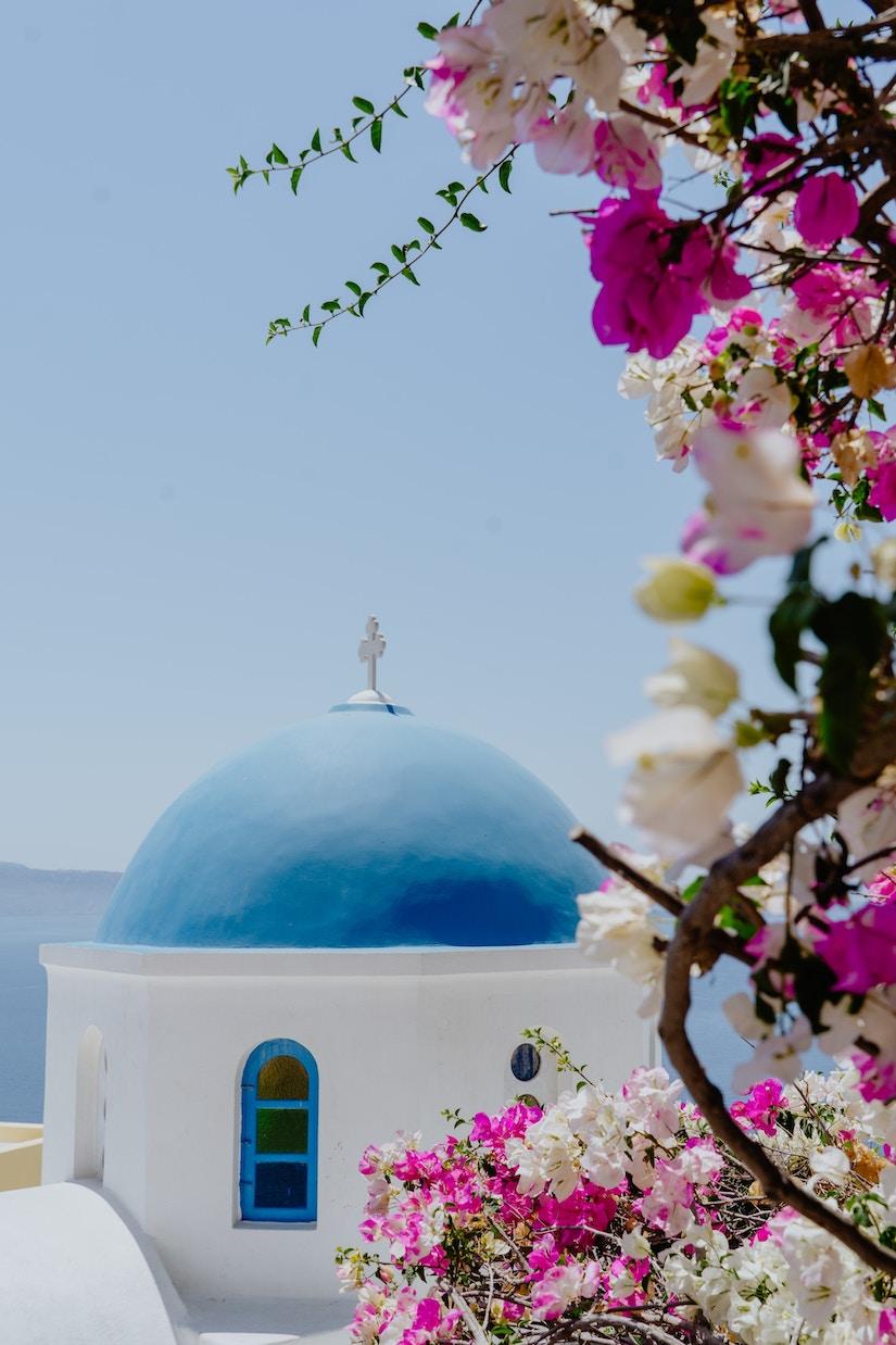 Weiß getünchtes Gebäute hinter Blumen am Mittelmeer