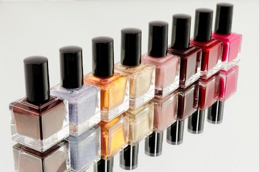 Aufgereihte gleichförmige Nagellackflaschen mit verschiedenfarbigem Inhalt
