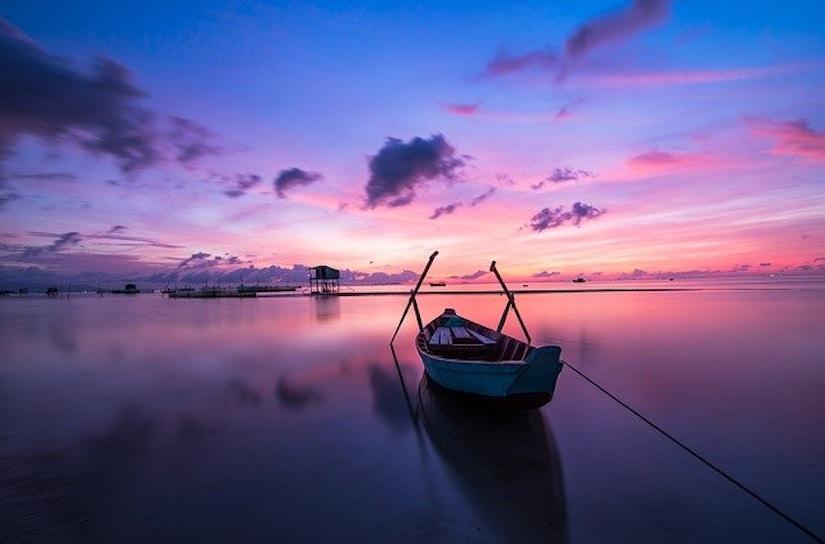 Ruderboot auf Wasser. Sonnenuntergang