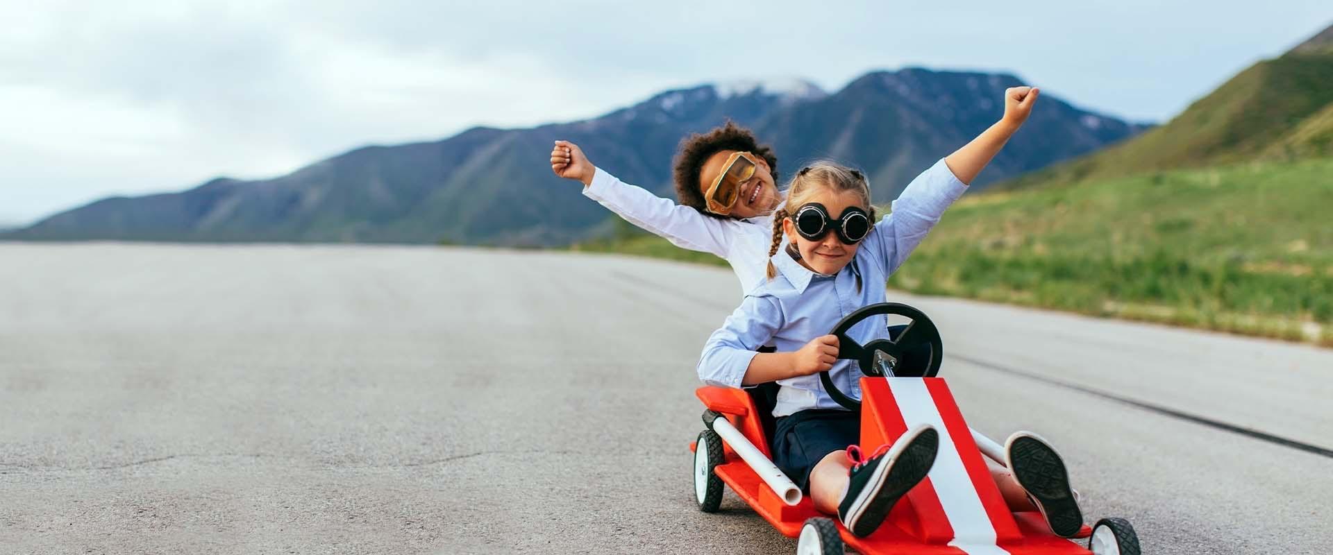 Ein Junge und ein Mädchen auf einem Spielzeug-Rennwagen.
