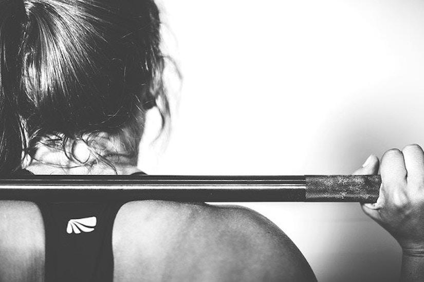 Rückenansicht von Frau mit Langhantelstange auf Schulter