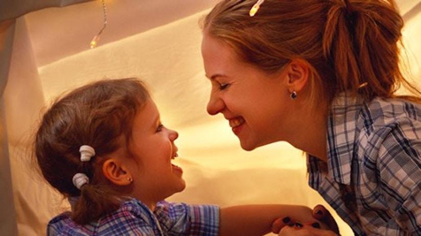 Eine Mutter und ihre Tochter schauen sich an und lächeln.