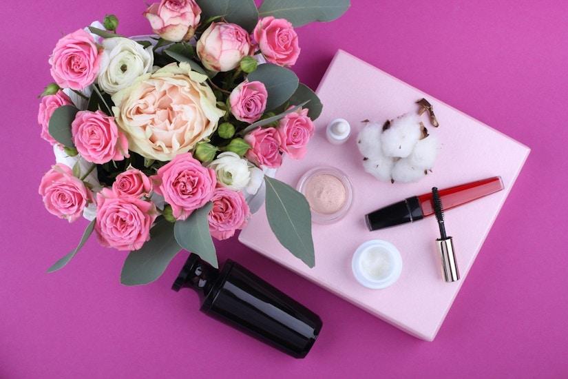 Kosmetik auf einem pinken Tisch mit Blumenstrauß.