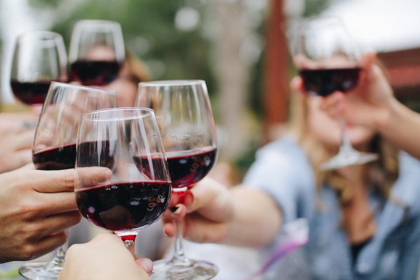 Mehrere Menschen prosten sich mit Rotweingläsern zu