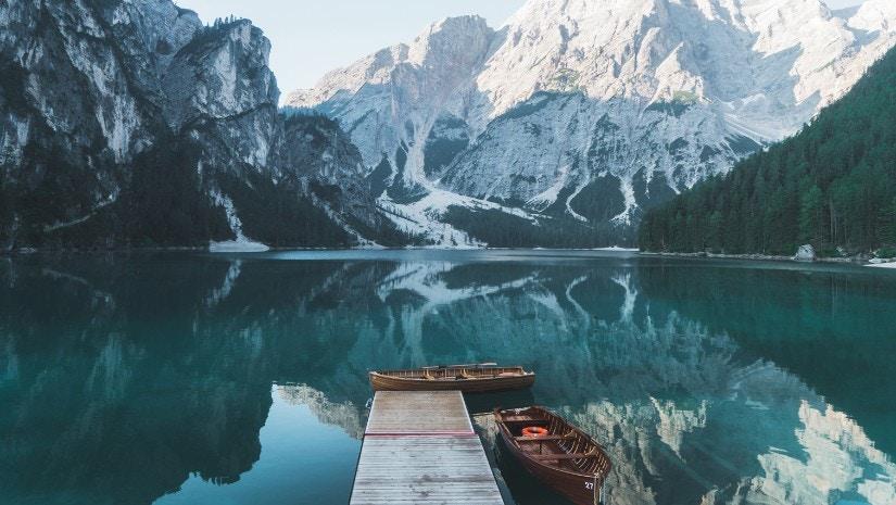 Ein See, der von Bergen umrandet ist mit einem Steg und zwei Boten auf dem Wasser.
