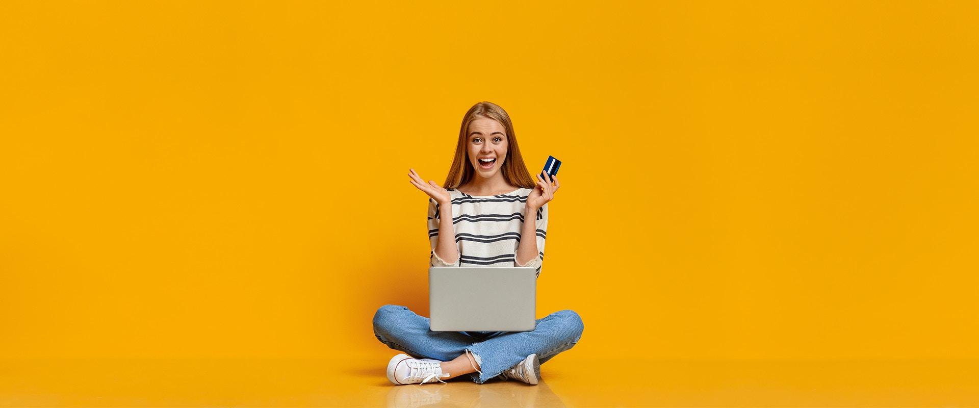 Singles' Day: Eine Frau sitzt auf dem Boden und hat eine Kreditkarte in der Hand und einen Laptop auf dem Schoß.
