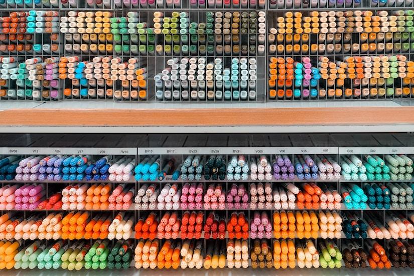 Farblich sortierte bunte Stifte in Regal