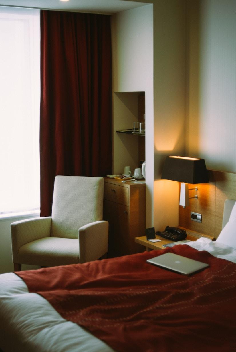 Stilvolles Hotelzimmer mit hellem Sessel und roten Gardinen