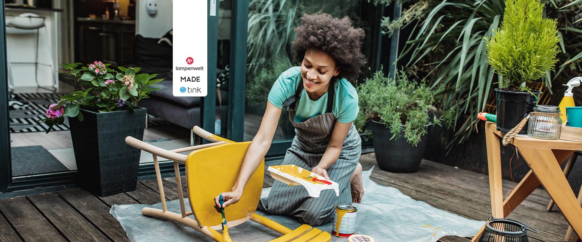 Eine Frau streicht einen Stuhl auf einem Balkon.