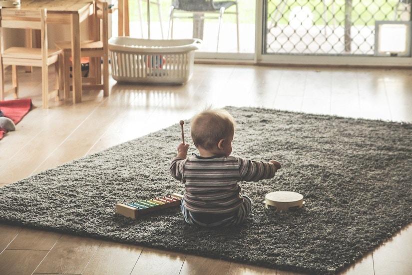 Baby sitzt auf flauschigem grauen Teppich und spielt einhändig Xylophon
