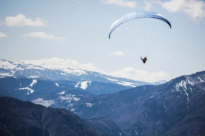 Person paragliding über den Bergen