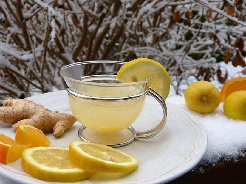 Tasse mit Ingwertee auf schneebedeckter Mauer. Umgeben von Zitronen und Ingwerstück.
