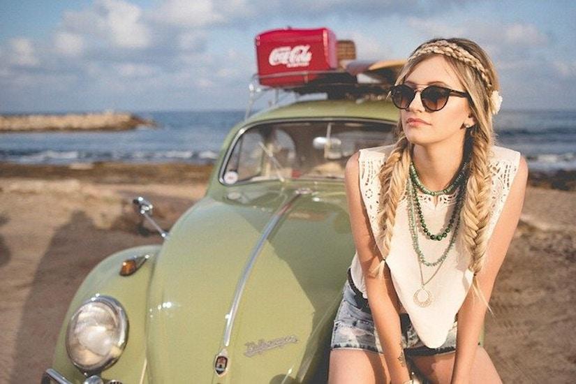 Modische Frau sitzt am Strand auf einem alten Beatle