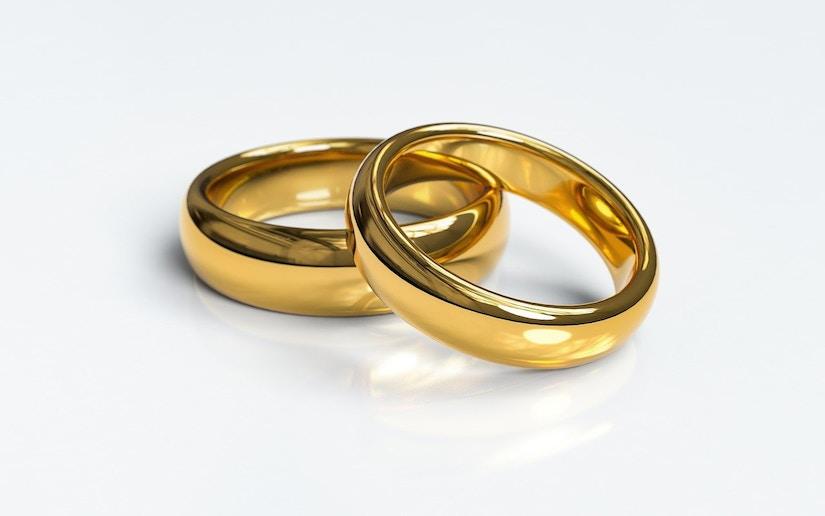 zwei goldene Trauringe aneinander gelehnt