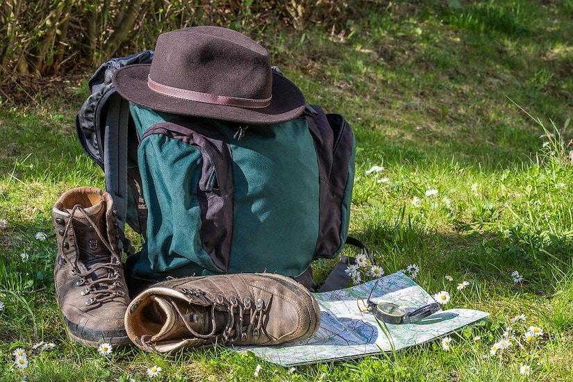 Rucksack, Hut, Karte und Kompass mit Wanderschuhen im Gras