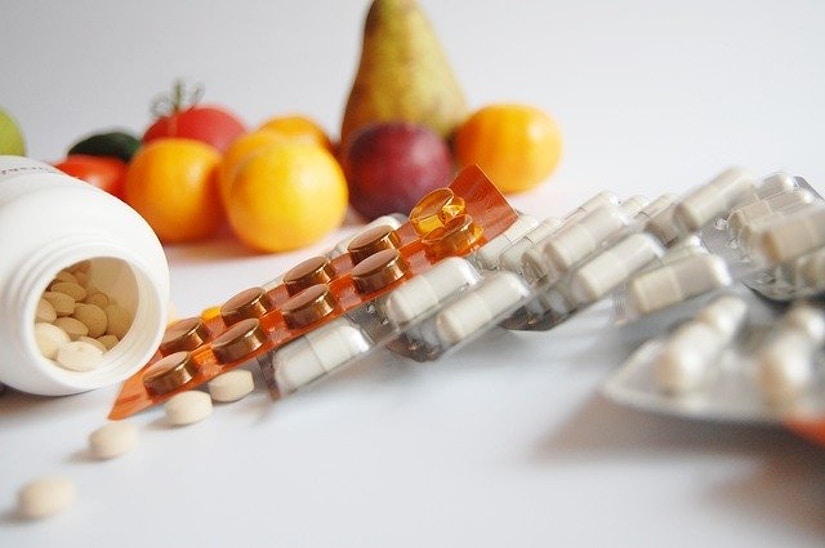 Verschiedene Tabletten vor Obst auf einer weißen Oberfläche.