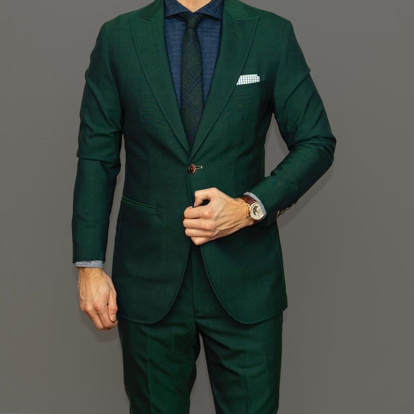 Mann in grünem Anzug mit dunkelblauem Hemd und schwarzer Krawatte