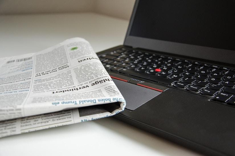 Zeitung liegt auf dem geöffneten Lapltop