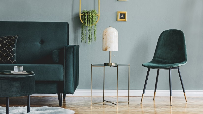 Ein Wohnzimmer mit einem grünen Samtsofa, einem grünen Samtstuhl, einem Tisch und einer Lampe.