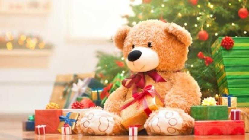 Ein Teddybär unter einem Weihnachtsbaum.