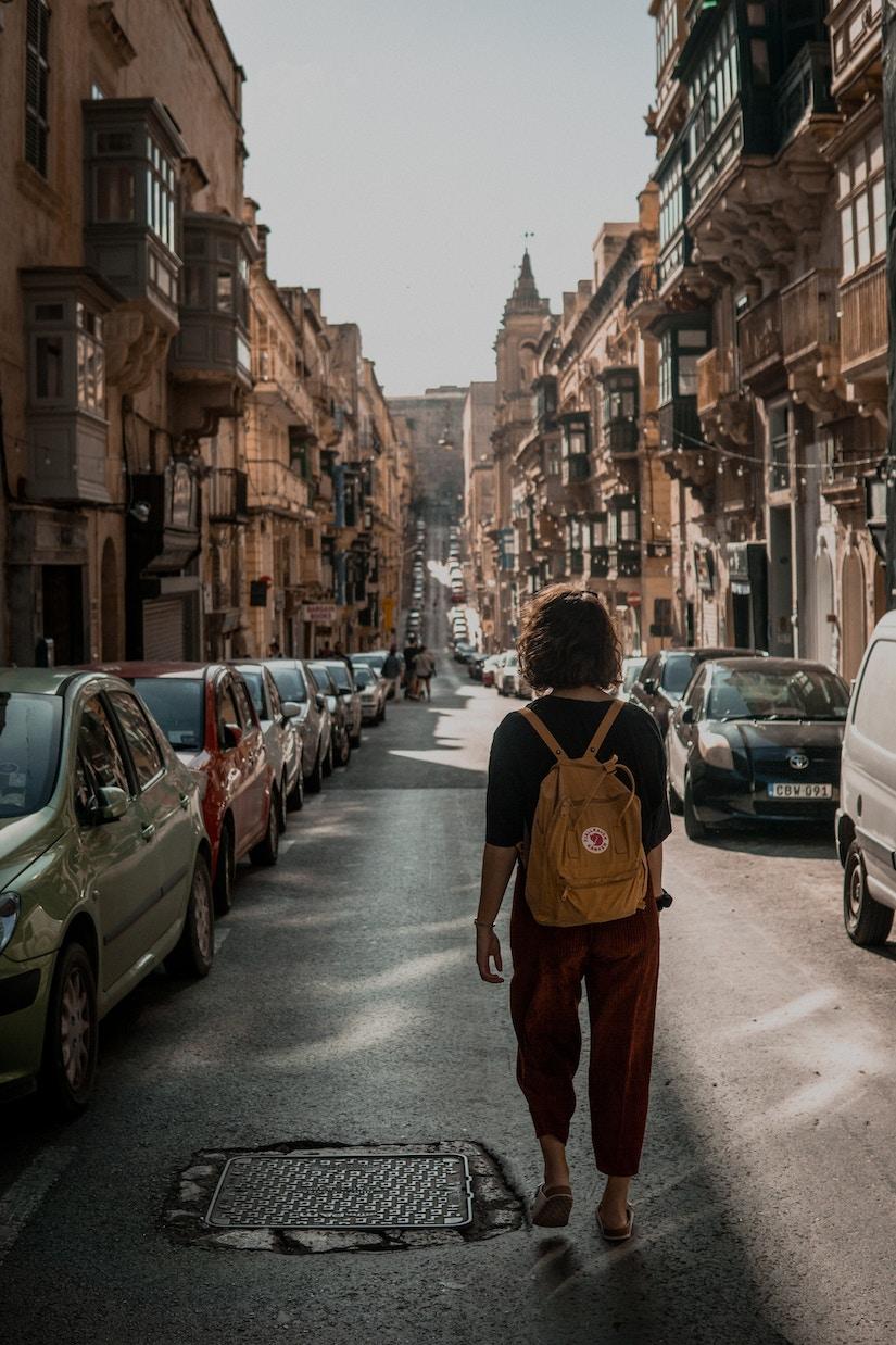 Frau mit Rucksack läuft durch mediterranen Straßenzug