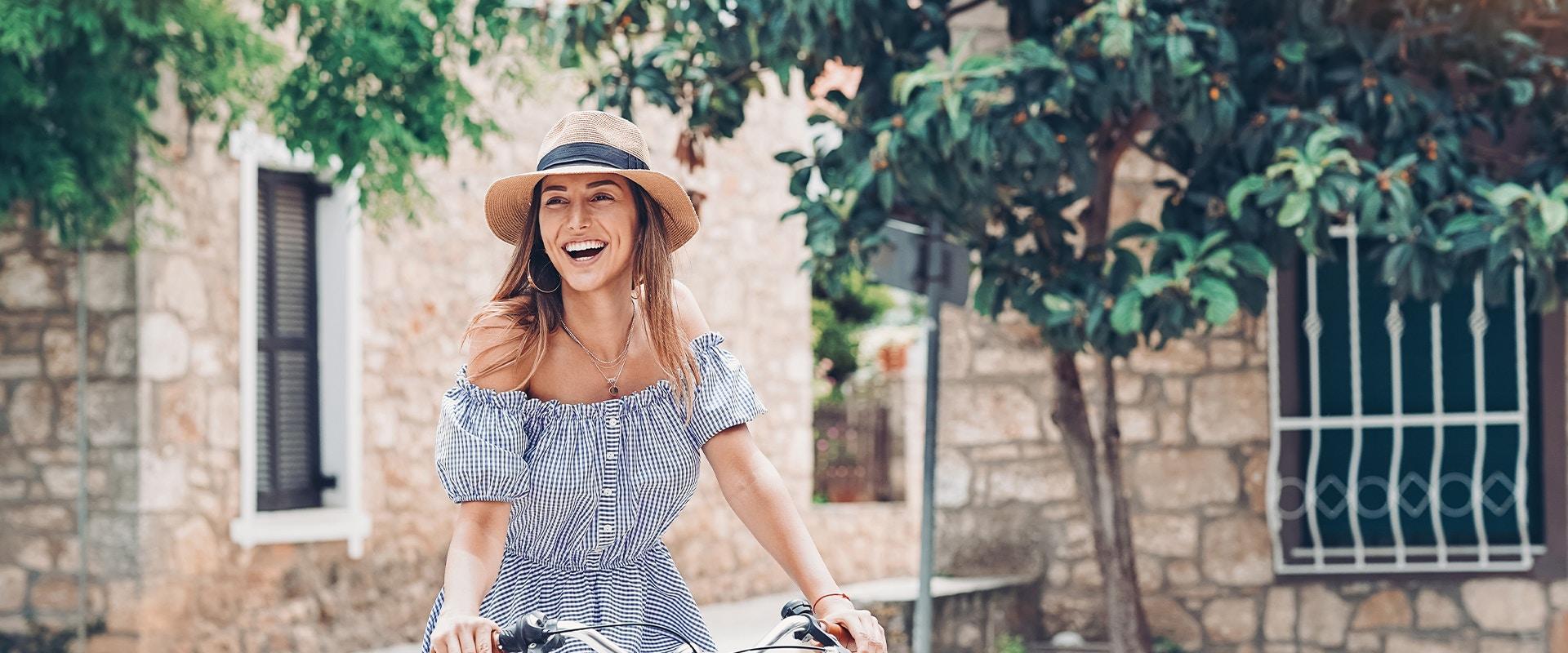 Eine Frau auf einem Fahrrad. Sie lacht.