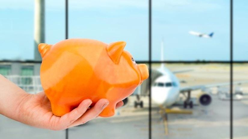 Eine Hand hält ein Sparschwein. Im Hintergrund sieht man Flugzeuge.