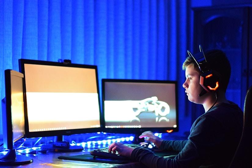 Jugendlicher Gamer sitzt im Dunkeln vorm PC Bildschirm