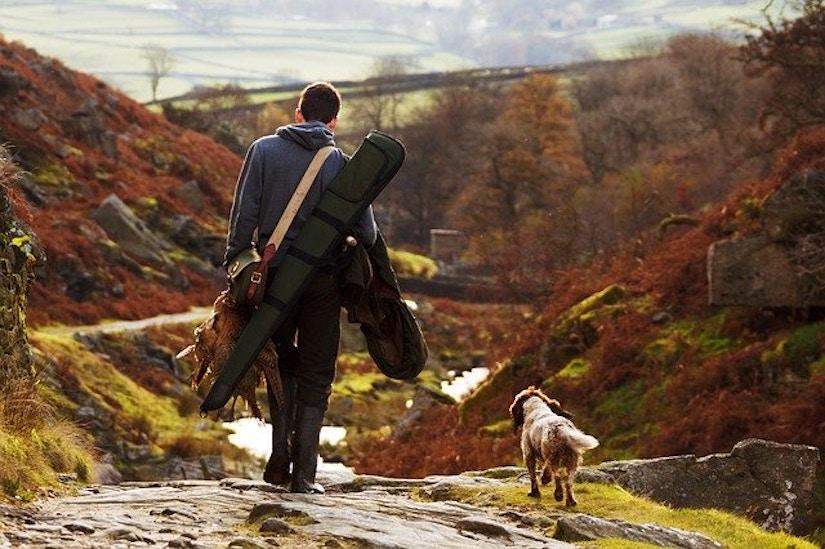 Jäger mit Hund in herbstlicher Landschaft