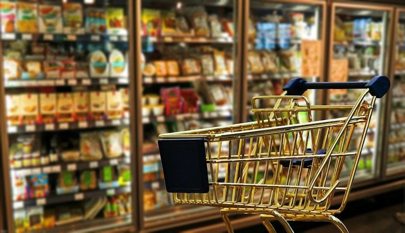 Goldener Einkaufswagen vor einem Kühlregal im Supermarkt