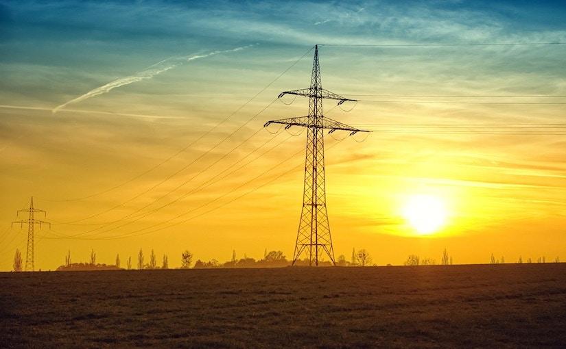 Stromleitungen auf dem Feld beim Sonnenuntergang