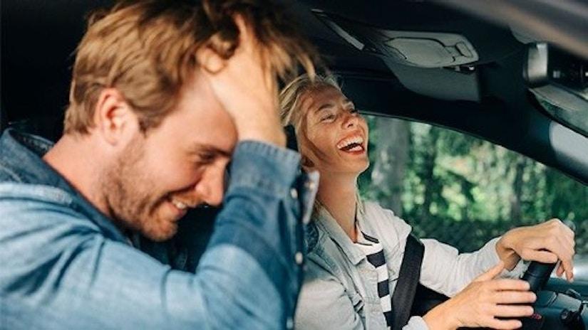 Ein Pärchen sitzt im Auto und lacht.