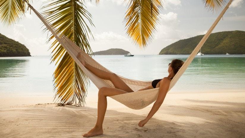 Eine junge Frau liegt in einer Hängematte und schaut aufs Meer.