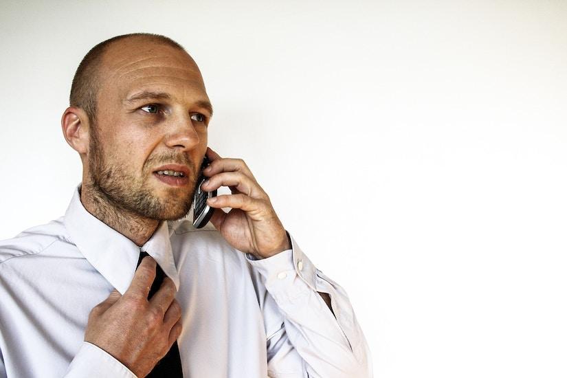 Erfolgreicher Geschäftsmann führt wichtiges Gespräch am Handy.
