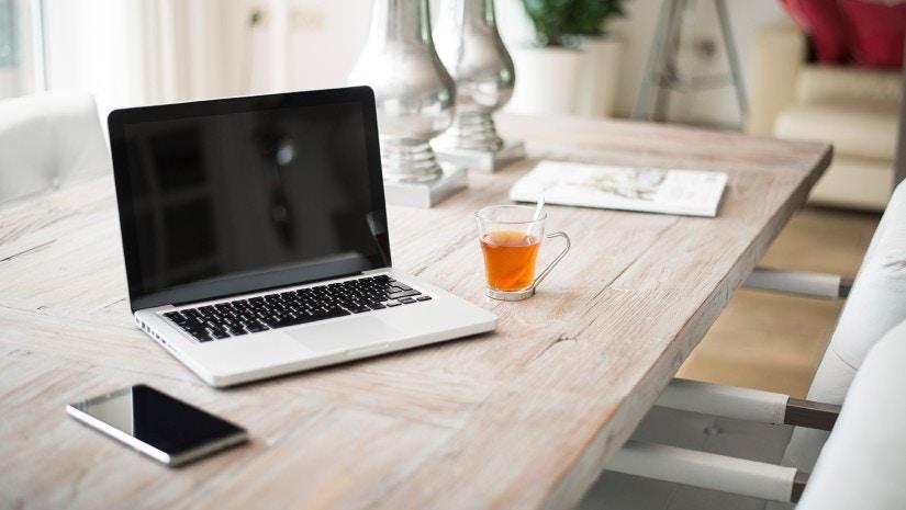 Ein Laptop steht offen auf einem Tisch. Daneben liegt ein Handy.