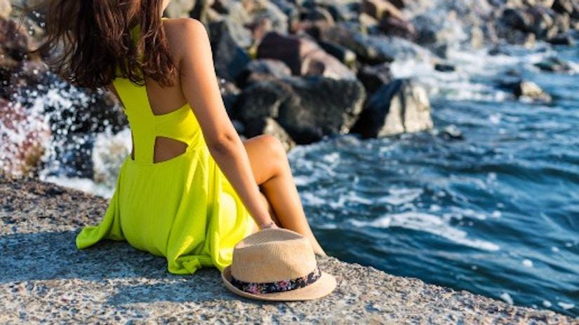 Eine Frau mit einem gelben Kleid mit Cut-Outs sitzt am Strand.
