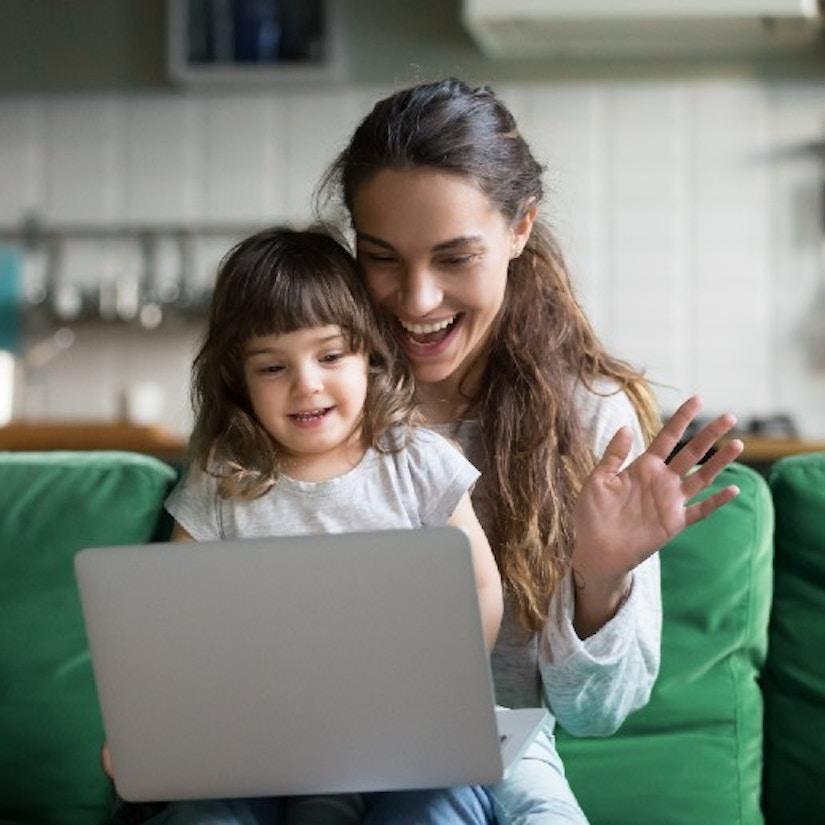 Eine Mutter hat ihre Tochter auf dem Schoß. Sie winken in die Kamera eines Laptops.
