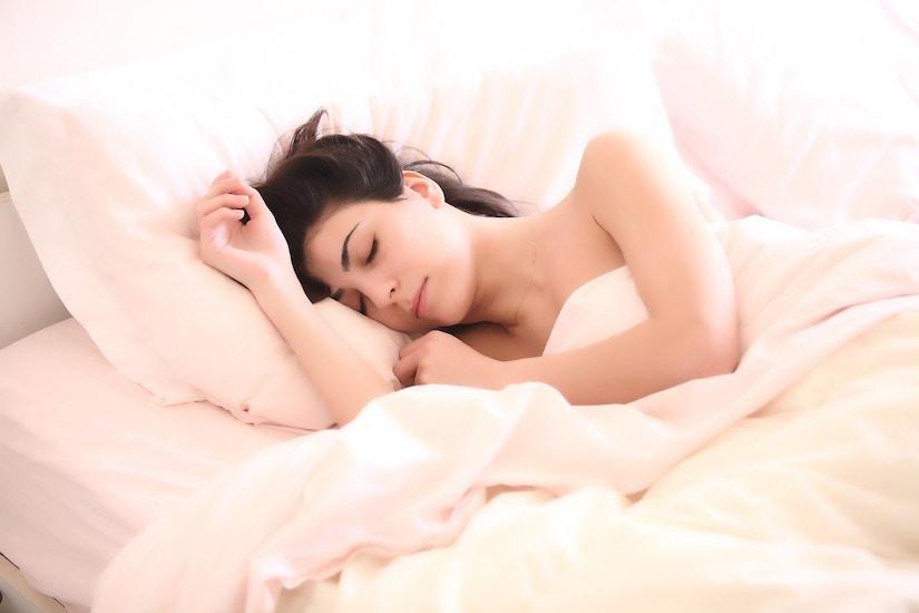 Frau schläft inmitten lachsfarbender Bettwäsche