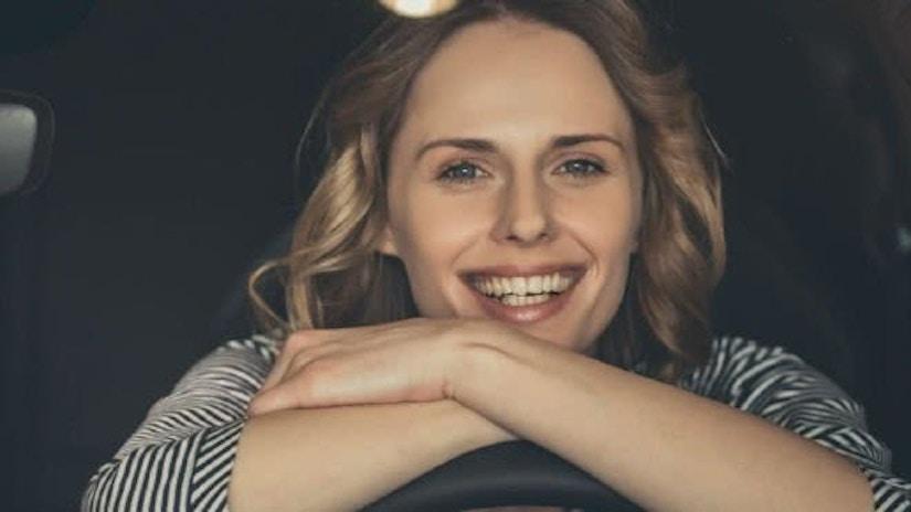 Frau stützt sich auf Lenkrad ab und freut sich
