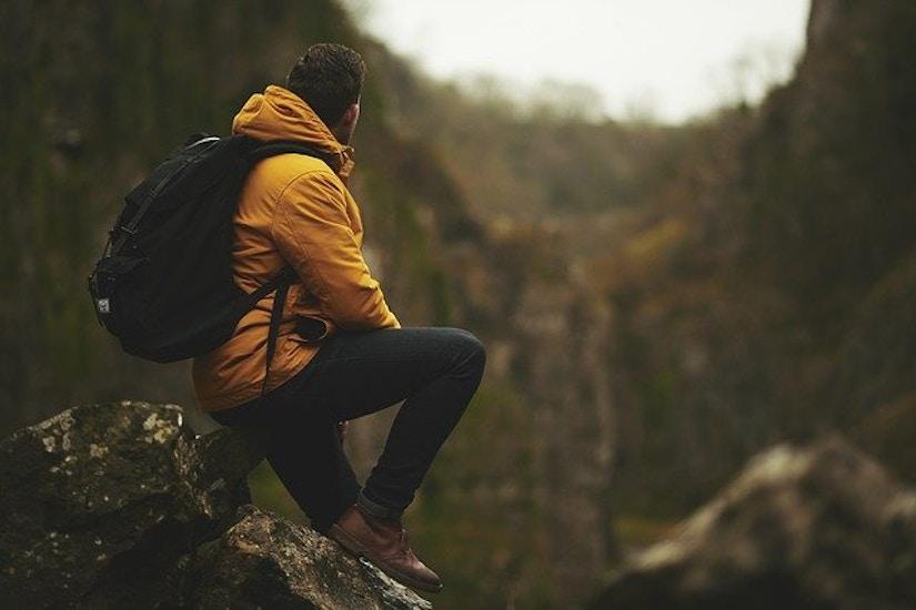 Wanderer mit gelber Jacke und Rucksack in den Bergen