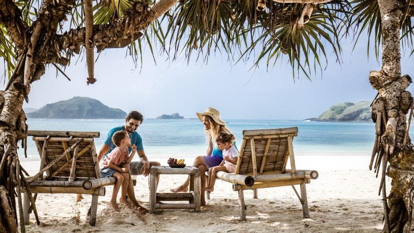 Eine Familie sitzt am Strand auf Holzpritschen unter Palmen und lacht.