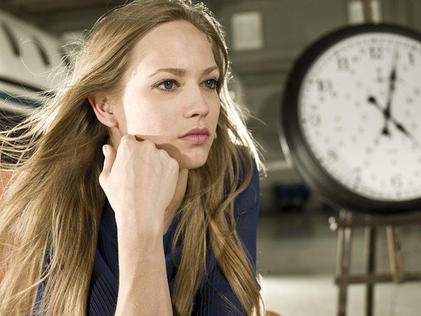 Frau modelt vor einer Standuhr